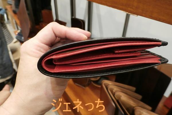 セドウィックのブライドルレザー2つ折り財布手に持つ
