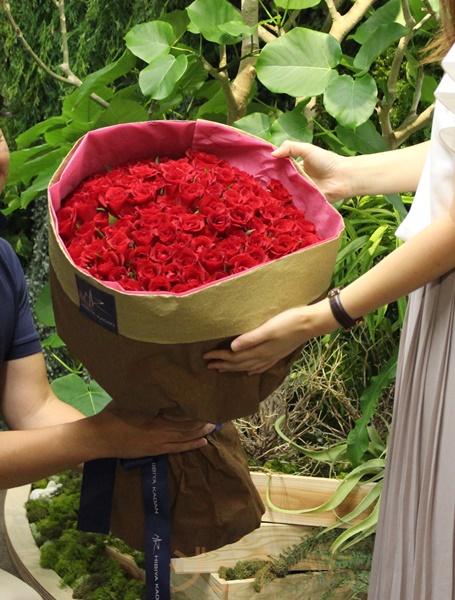 100本の赤いバラ花束渡すイメージ
